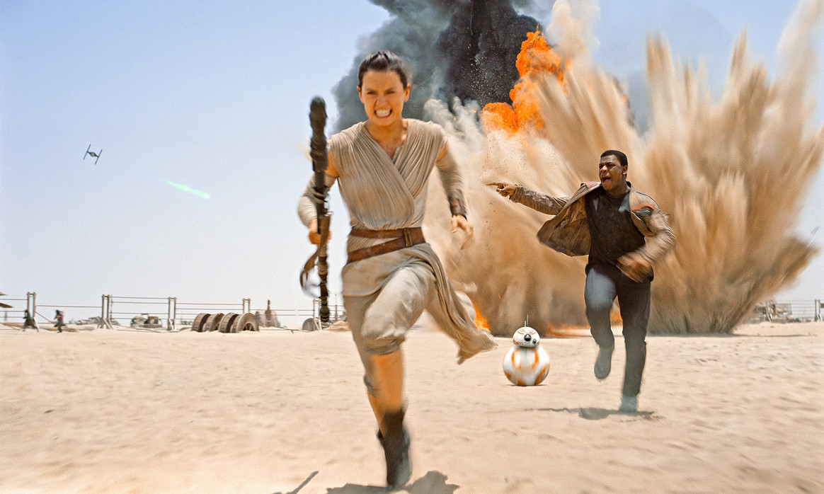 Rey (Daisy Ridley) and Finn (John Boyega) flee an explosion in Star Wars Episode VII The Force Awakens (2015)