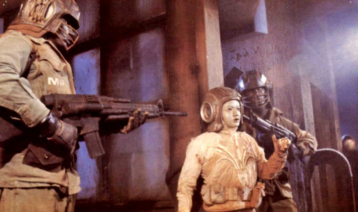 The android Grid (Deep Roy) surrounded by military droids in Starship (1984)