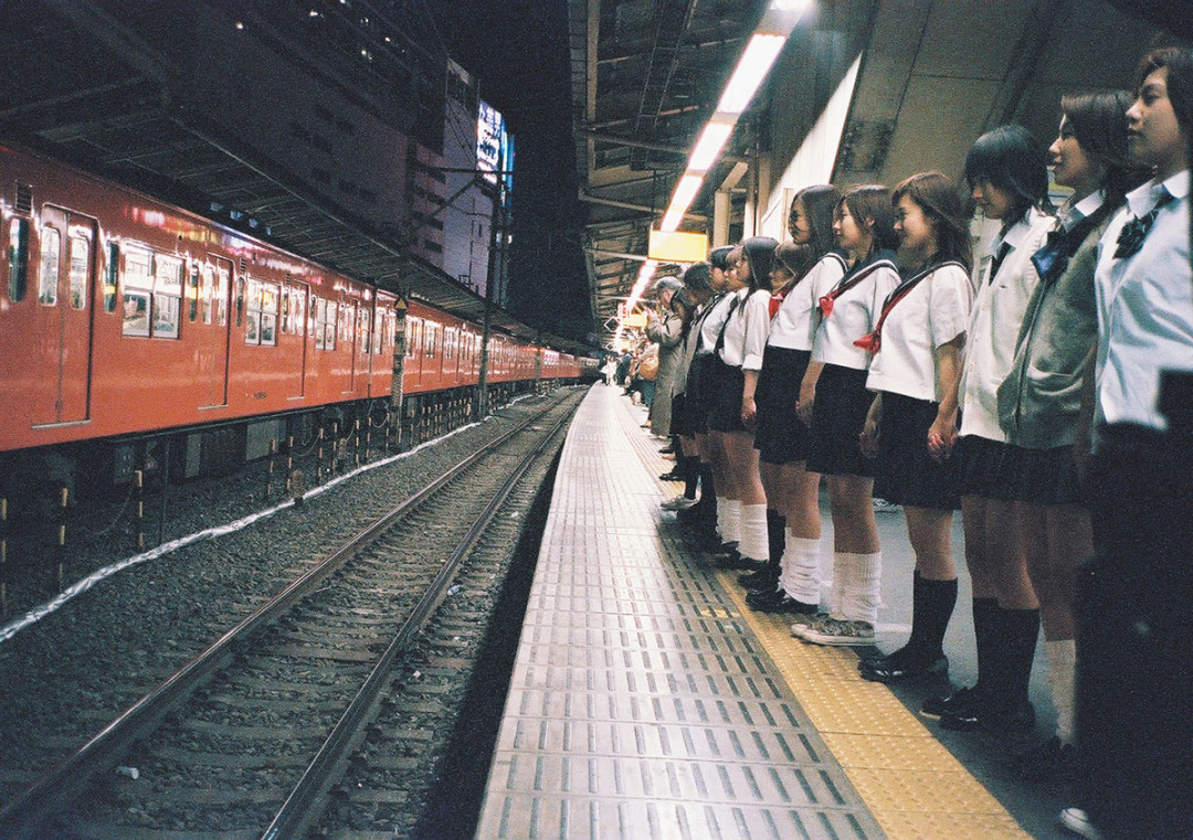 Japanese schoolgirls lined up on a railway platform to commit mass suicide in Suicide Club (2002)