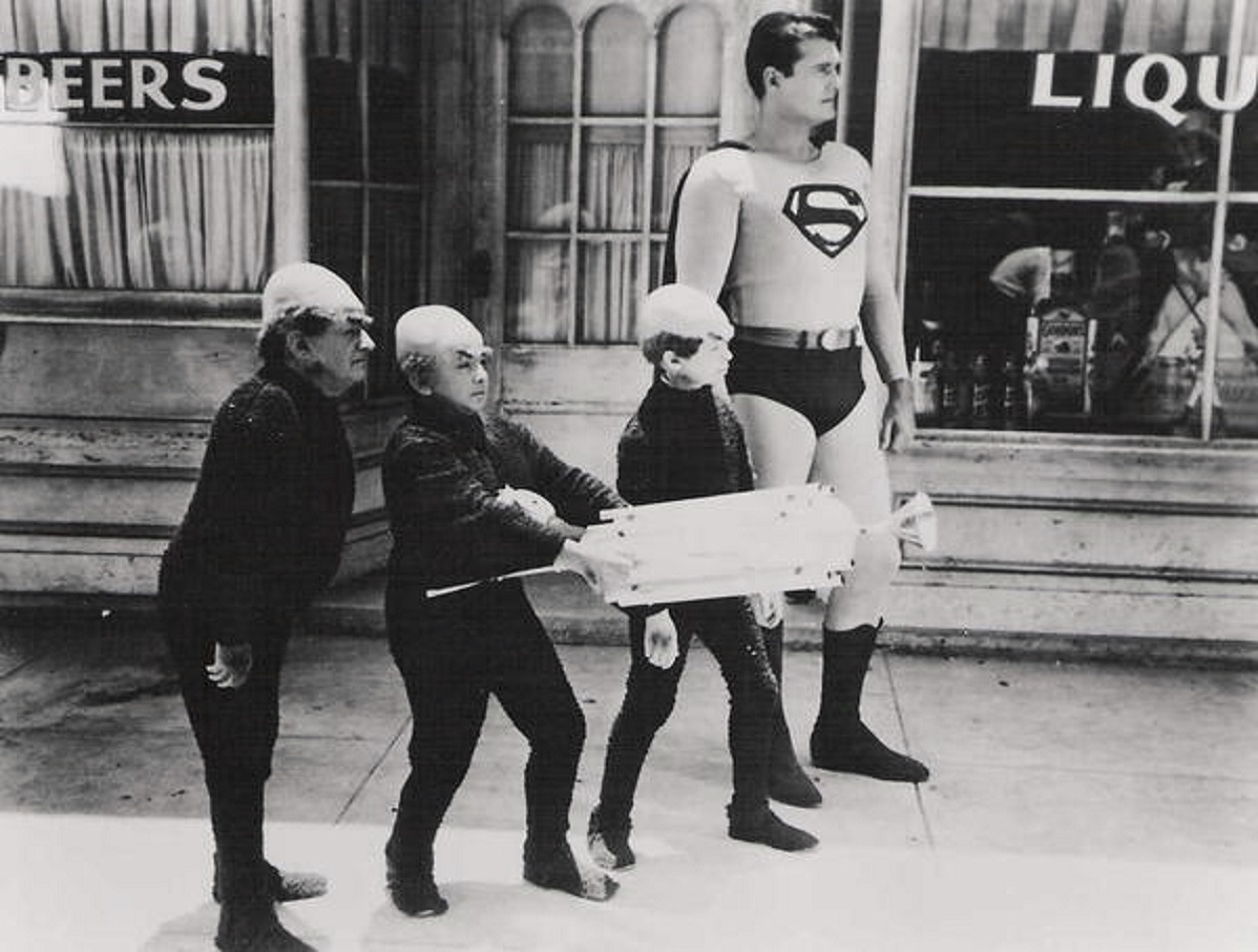 Superman (George Reeves) accompanied by the Mole-Men