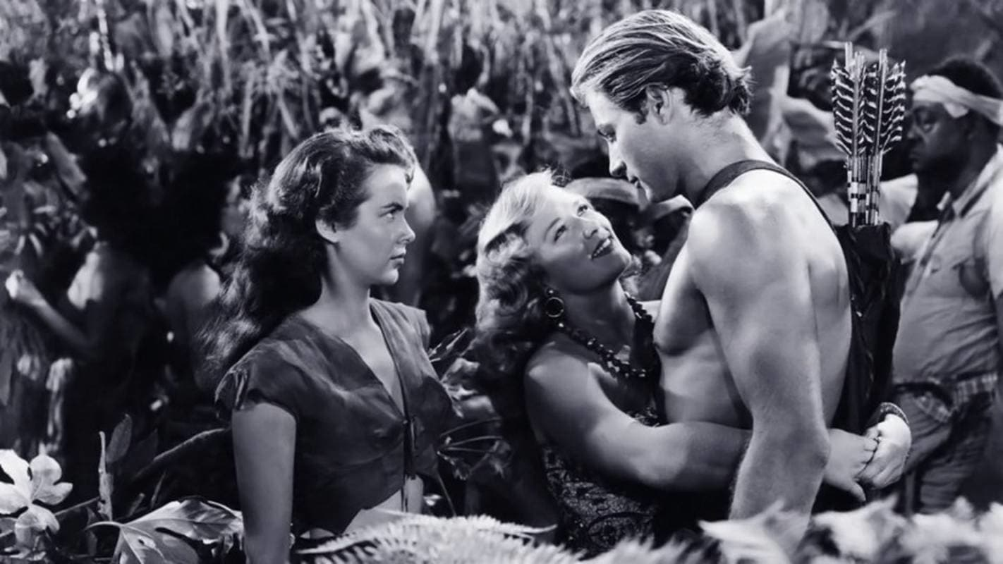 A none-too-happy Jane (Vanessa Brown) looks on as Lola (Denise Darcel) hugs Tarzan (Lex Barker) in Tarzan and the Slave Girl (1950)