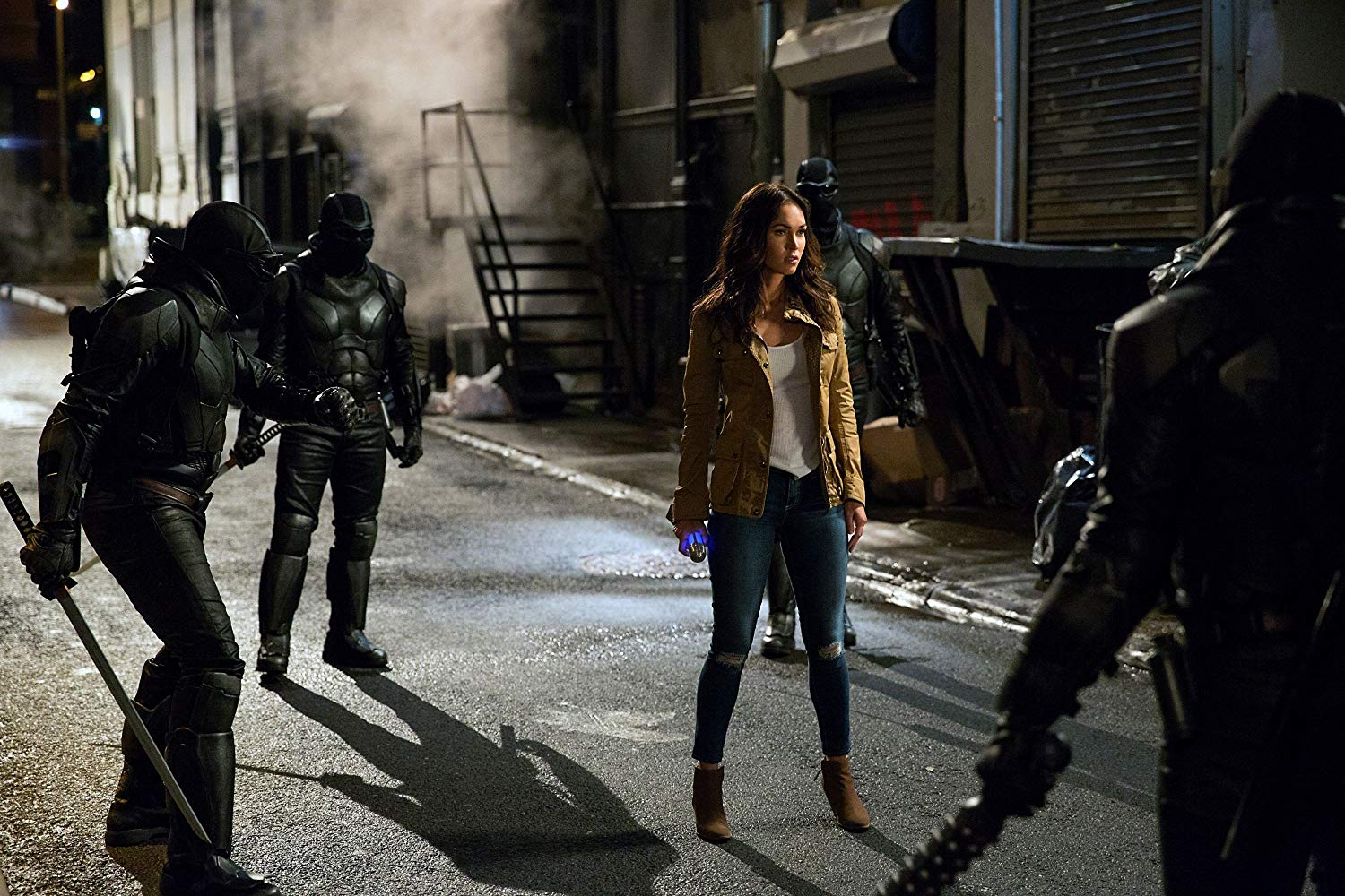 April O'Neil (Megan Fox) surrounded by members of The Foot in Teenage Mutant Ninja Turtles: Out of the Shadows (2016)