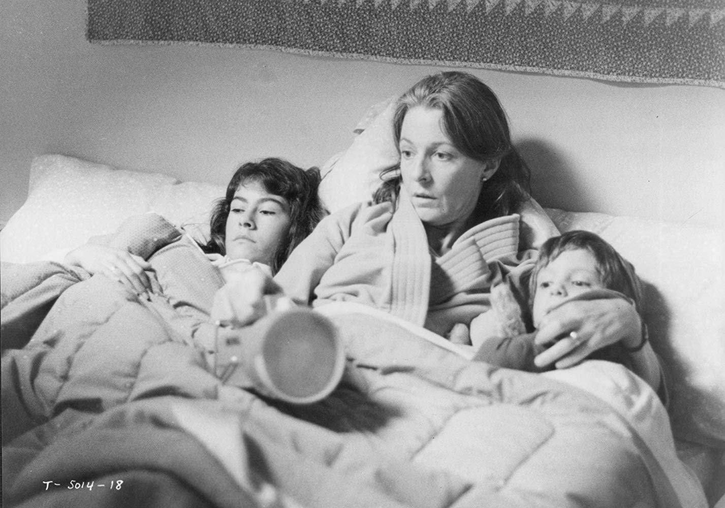 Mother Jane Alexander (c) huddles in bed with daughter Roxana Zal (l) and son Lukas Haas (r) in Testament (1983)