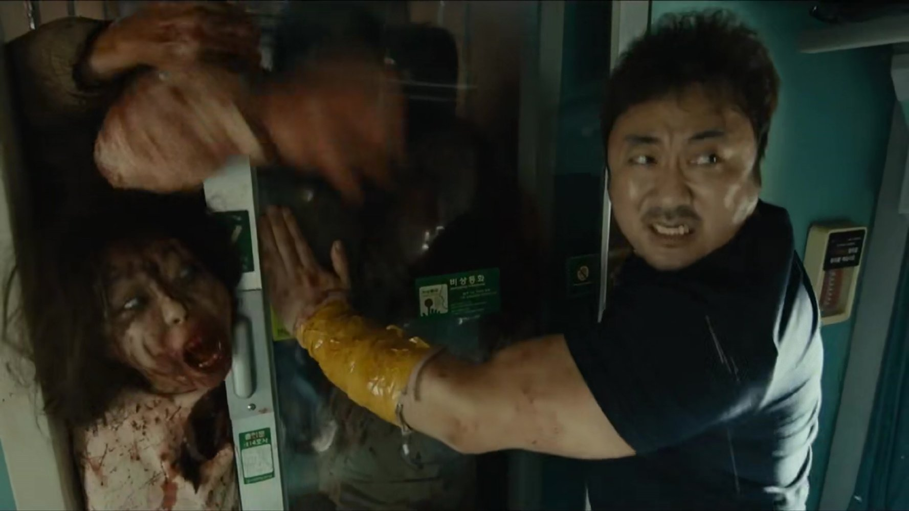Dong-seok Ma tries to hold back the zombie horde in Train to Busan (2016)