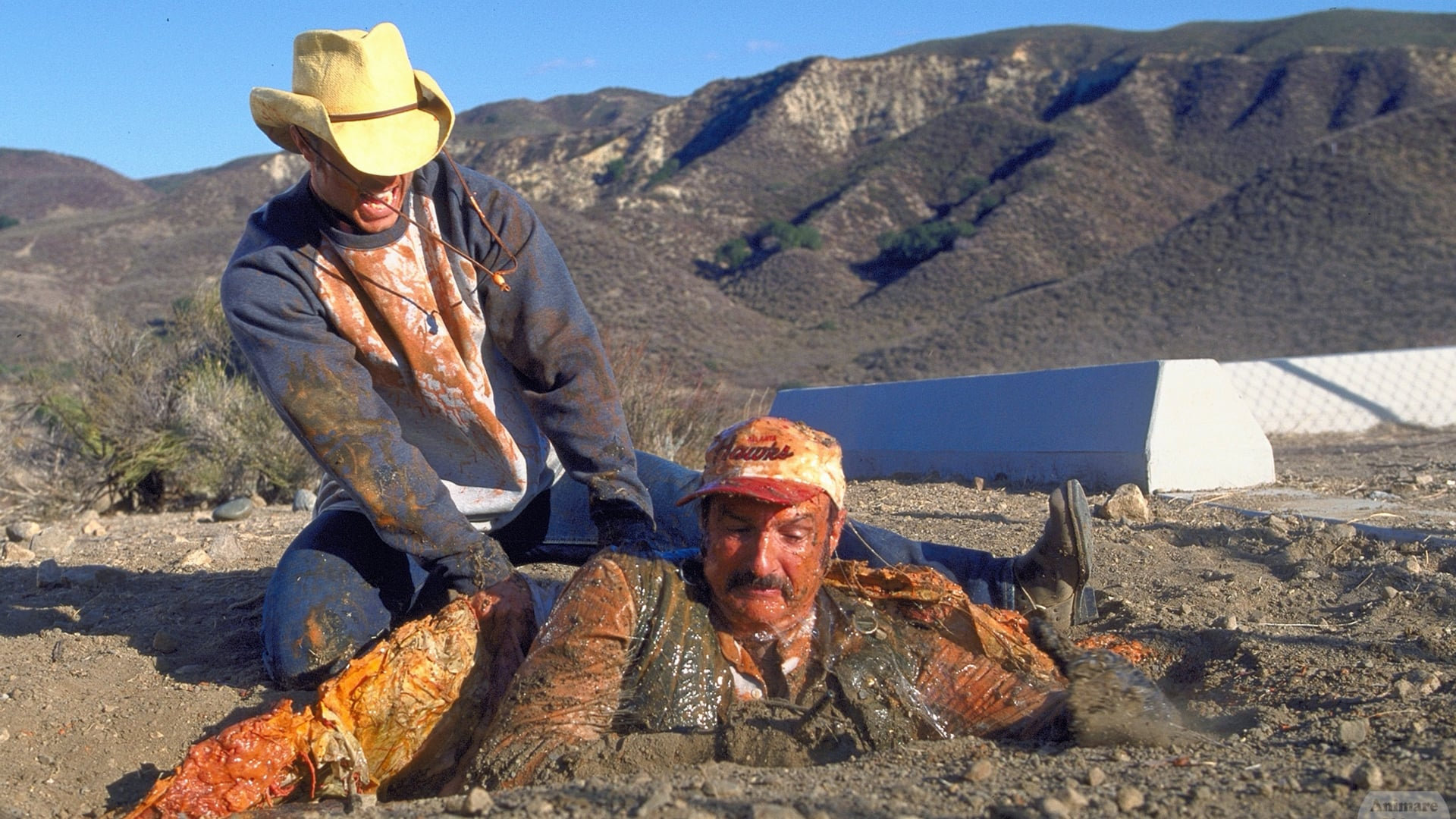 Shawn Christian tries to rescue Michael Gross from being swallowed by a Graboid in Tremors 3: Back to Perfection (2001)
