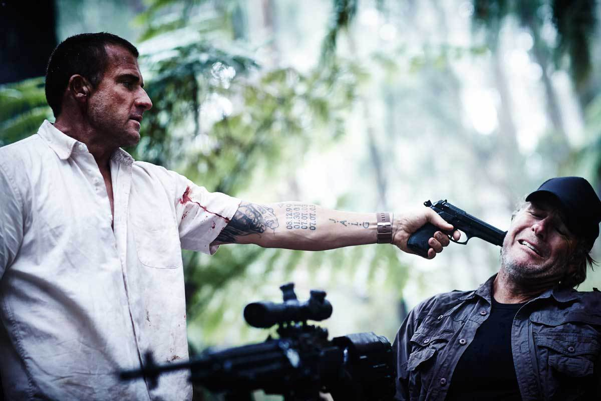 Dominic Purcell as Rick Tyler, a Navy SEAL forced into a barehands survival game, holds a gun to hunter Robert Taylor in Turkey Shoot (2014)