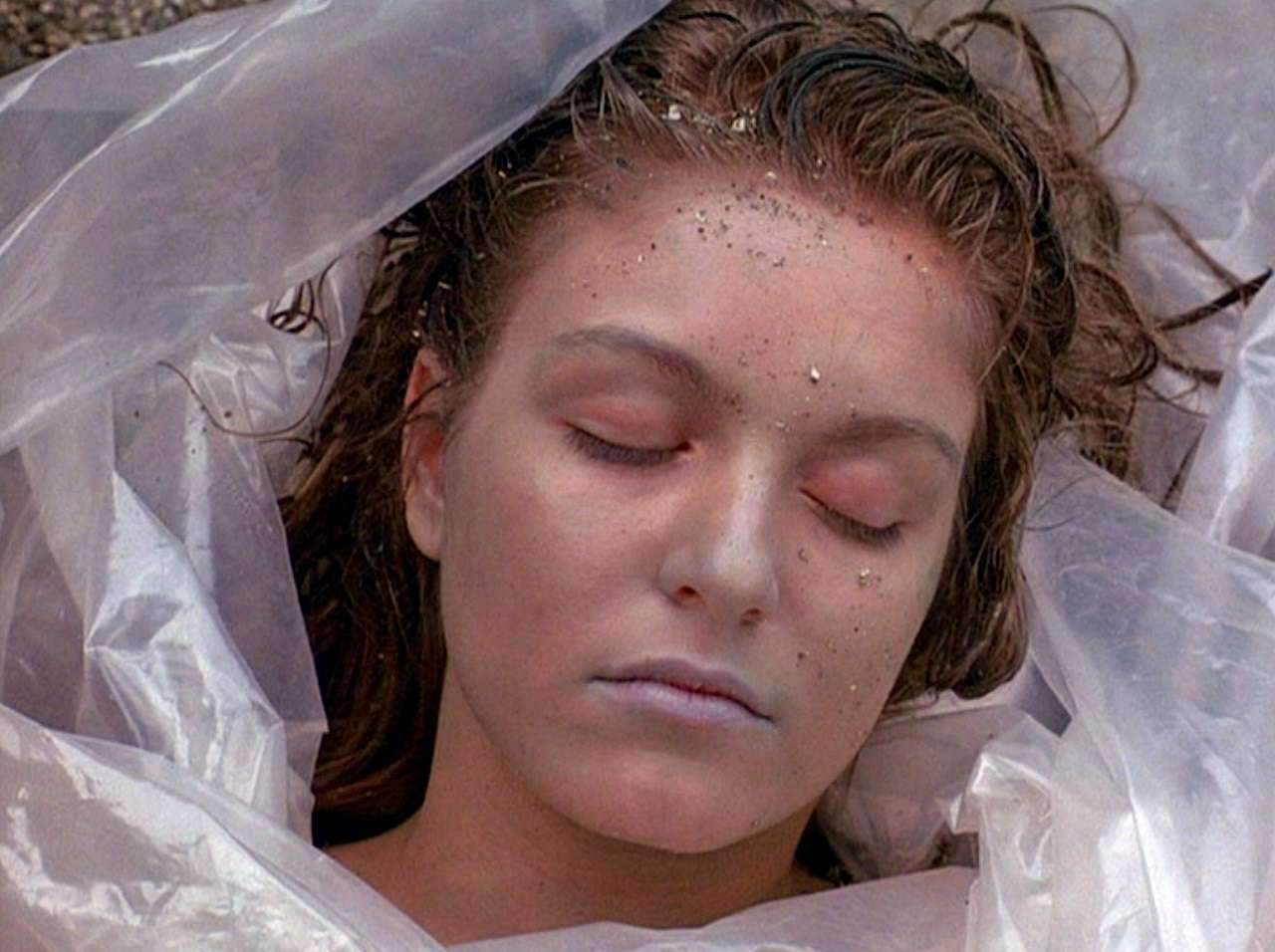 Laura Palmer (Sheryl Lee)'s dead body wrapped in plastic by the lakeside in Twin Peaks (1990)