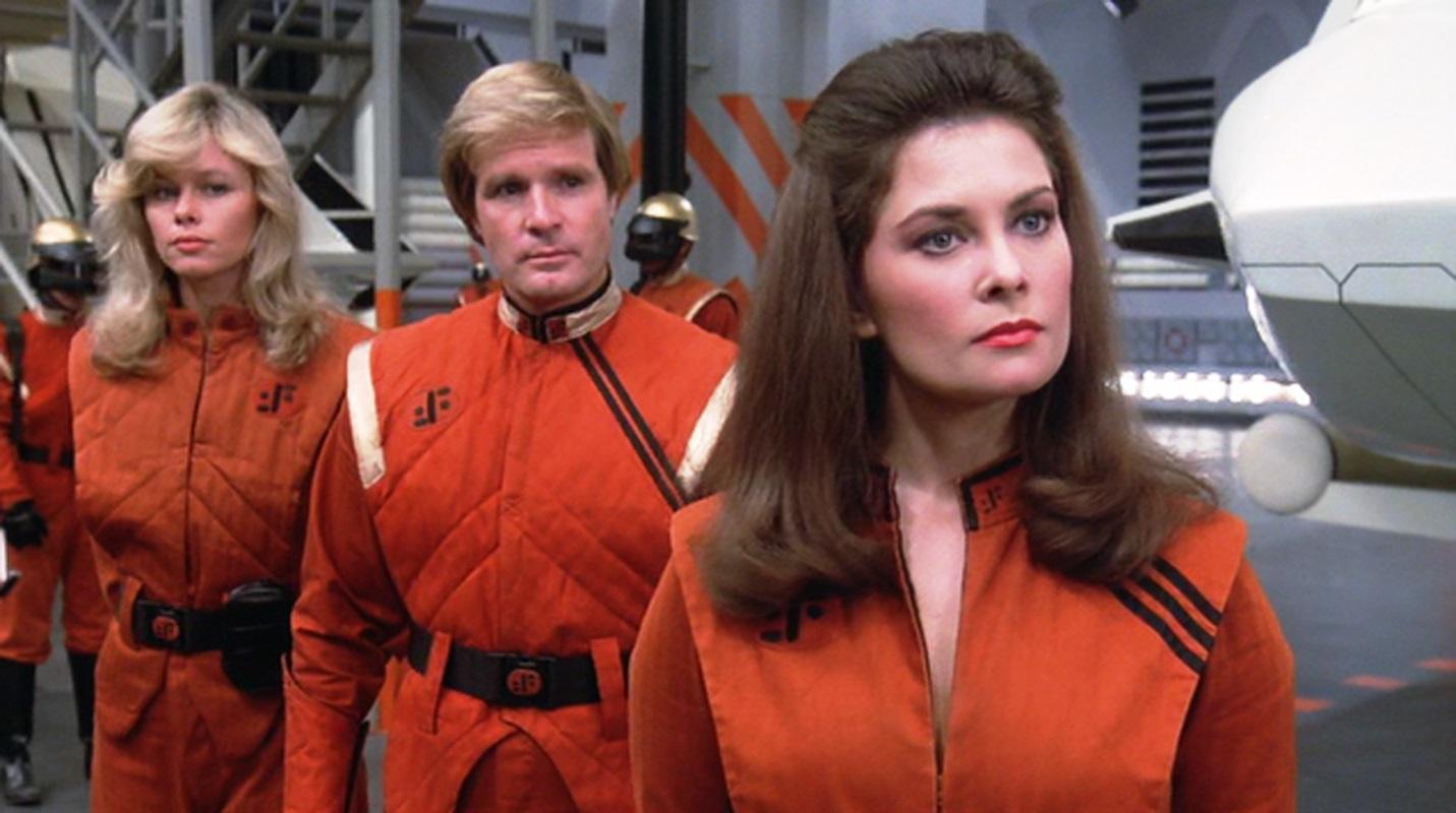 The Visitor leader Diana (Jane Badler) (r) with Martin (Frank Ashmore) behind her in V (1983)