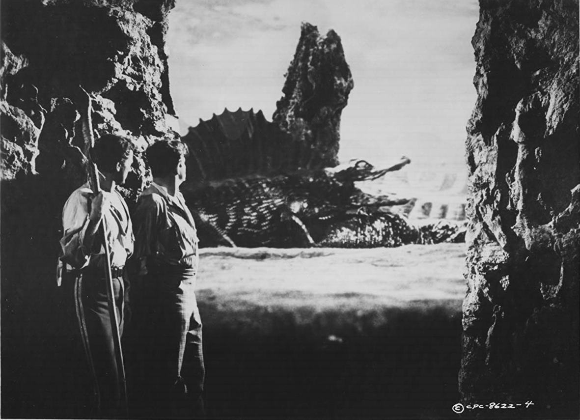 (l to r) Cesare Danova and Sean McClory view prehistoric life after being swept off on a comat in Valley of the Dragons (1961)