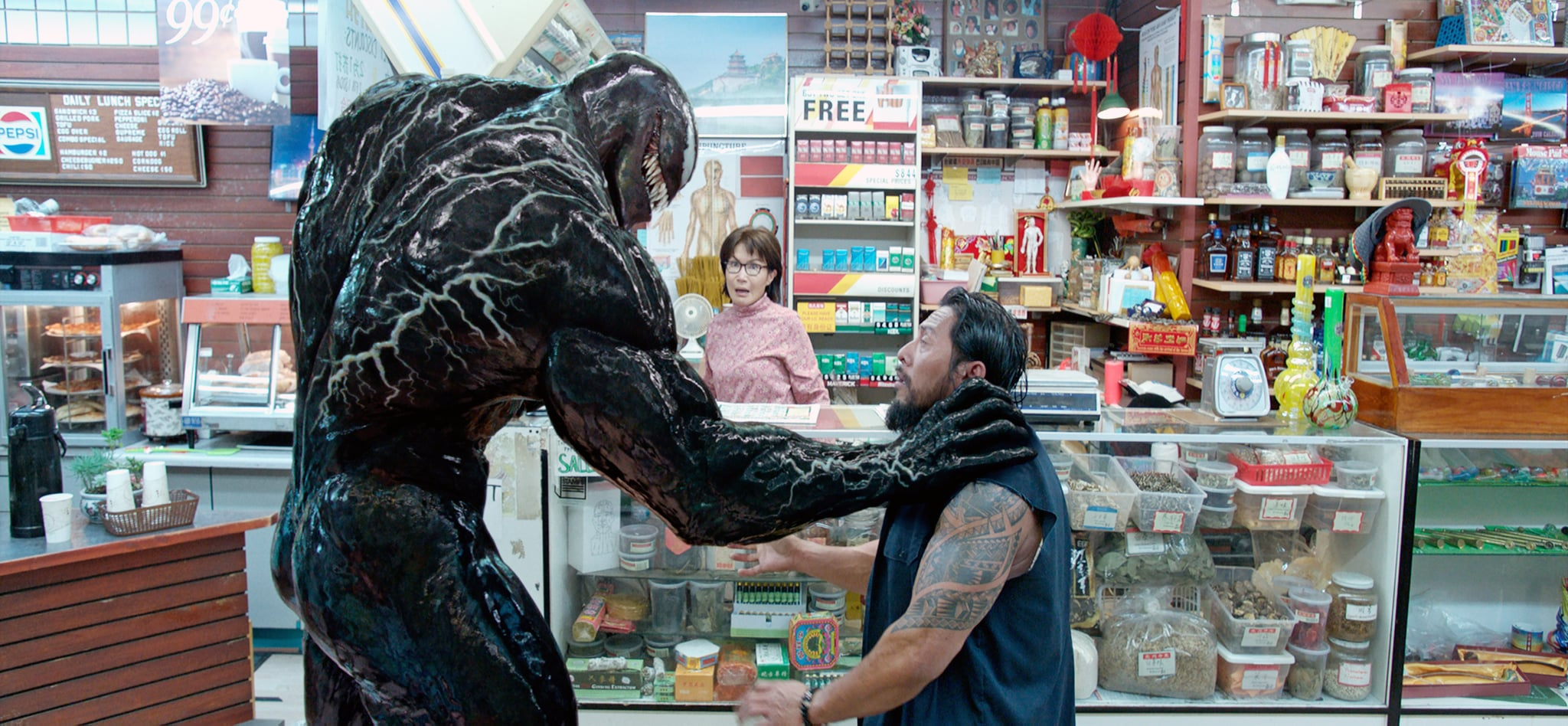 Venom (Tom Hardy) deals with a petty hood while convenience store owner Mrs Chen (Peggy Lu) looks on in Venom (2018)