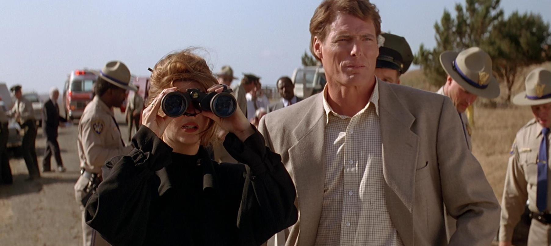 Christopher Reeve and Kirstie Alley (behind binoculars) watch from the military cordon line in Village of the Damned (1995)