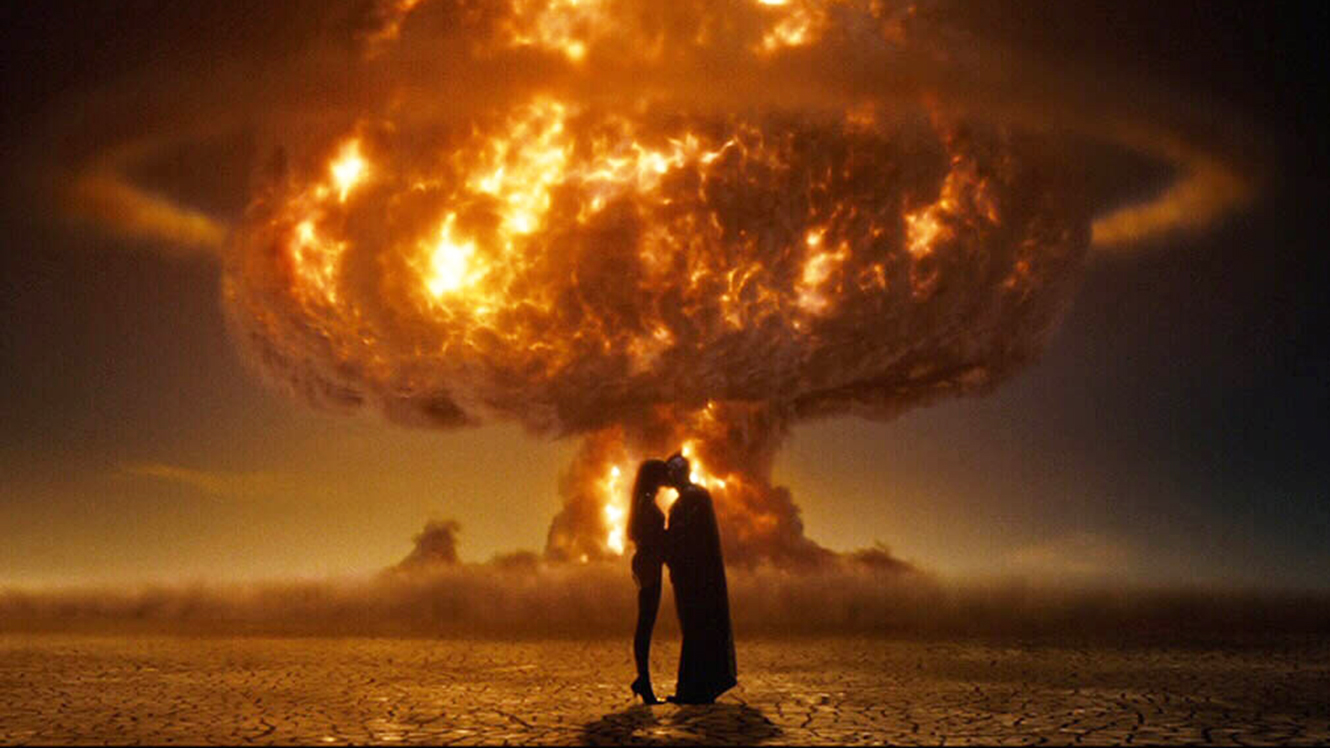 Iconic image of Scarlet Spectre and Nite Owl kissing silhouetted against an atomic bomb in Watchmen (2009)