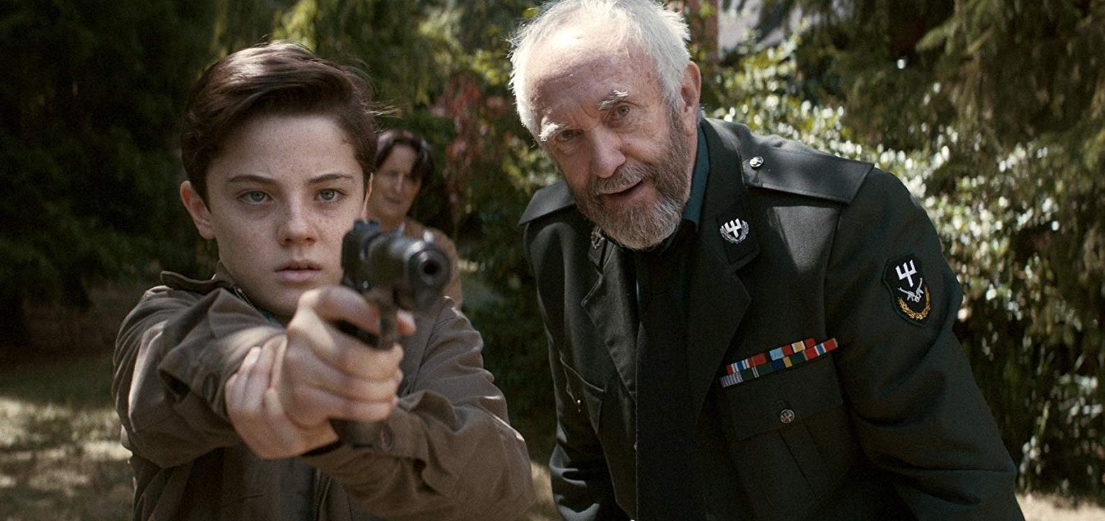 Young Djarta (Lorenzo Allchurch) is taught how to use a gun by his grandfather Jonathan Pryce. With grandmother Fiona Shaw lurking in the background in The White King (2016)