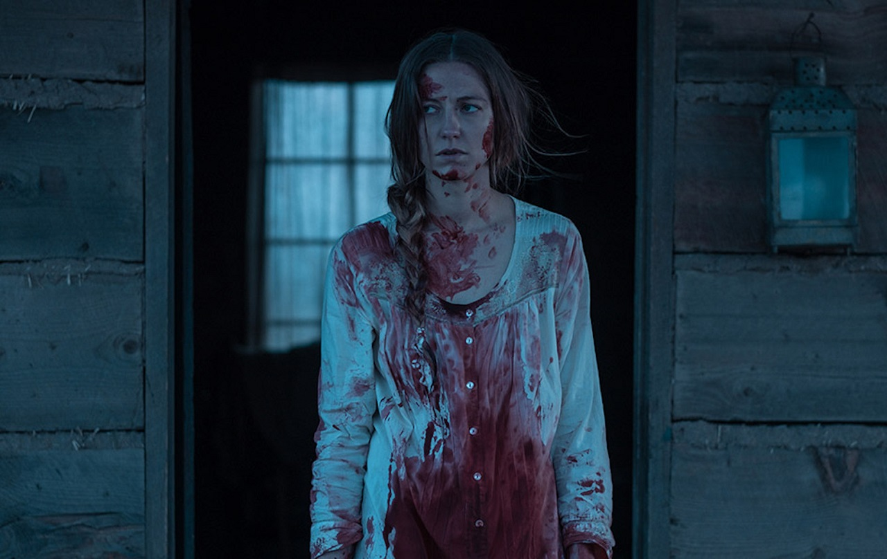 Caitlin Gerard alone in the cabin on the prairies haunted by possibly imagined demons in The Wind (2018)
