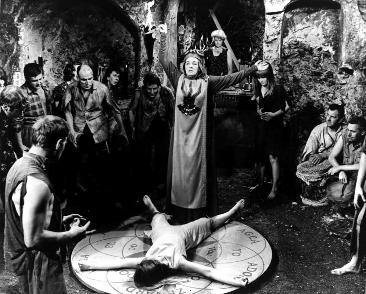The witches conduct their ritual as the group's leader Kay Walsh (c) stands over a sacrificial Ingrid Brett in The Witches (1966)