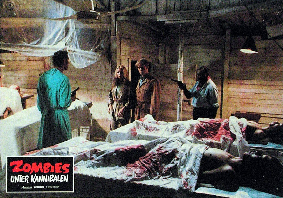 (l to r) Mad scientist Donald O'Brien amd prisoners Alexandra Delli Colli and Ian McCulloch, along with the doctor's henchman Dakar in Zombie Holocaust (1980)