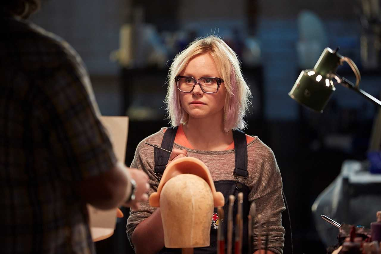 Alison Pill as the sex-doll factory worker lamenting her small breast size in Zoom (2015)