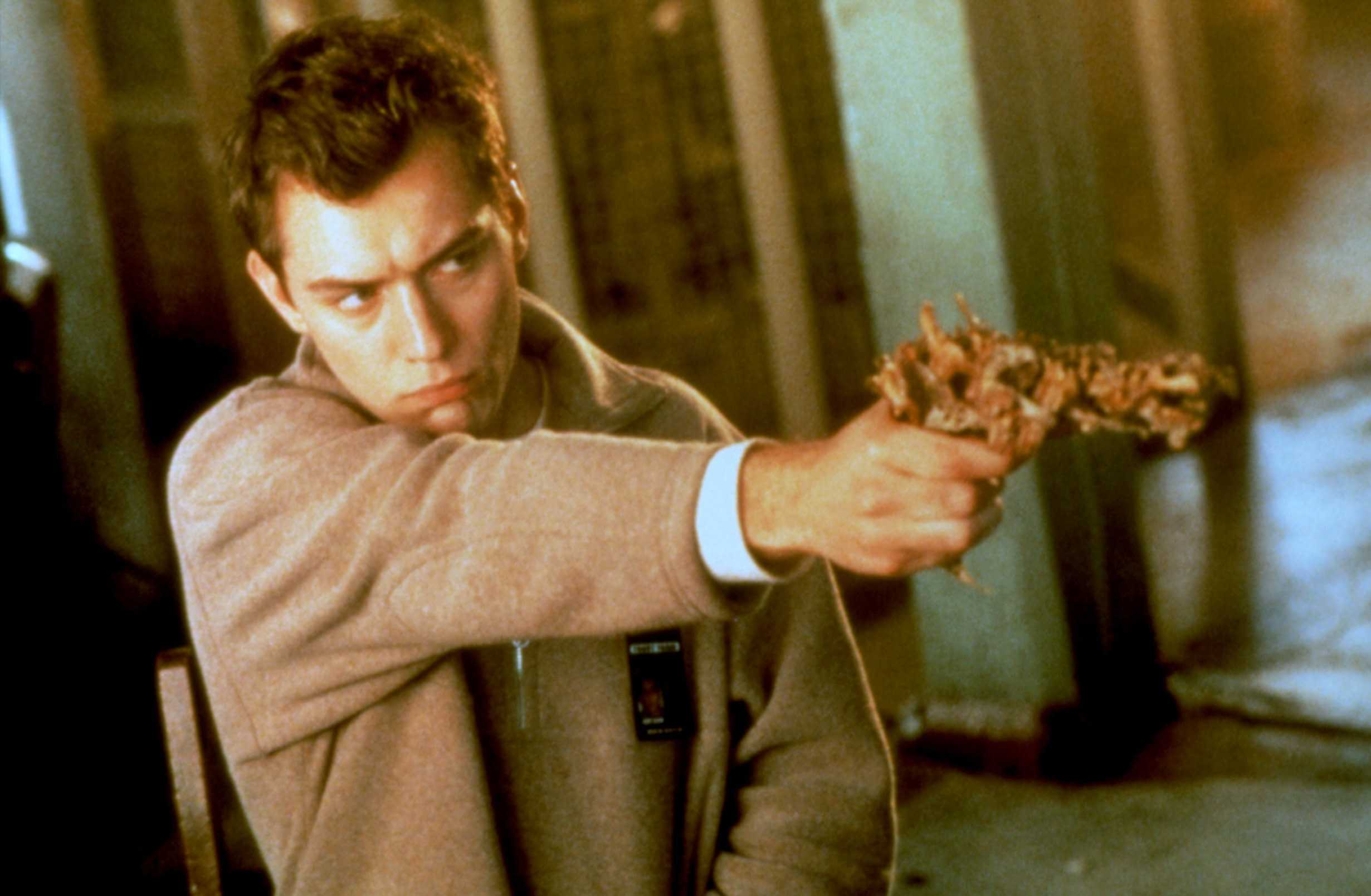 Ted Pikul (Jude Law) wields an organic gun in eXistenZ (1999)